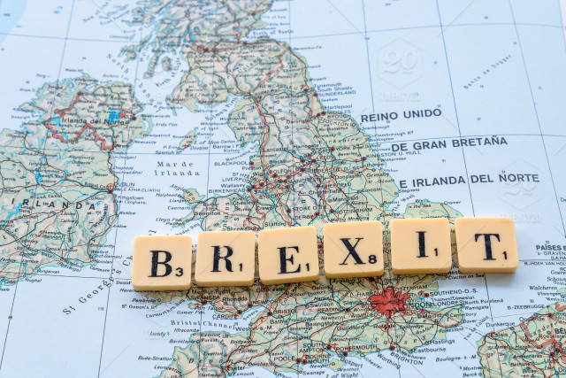Scrabble letters spelling 'Brexit' with a map of the UK as background