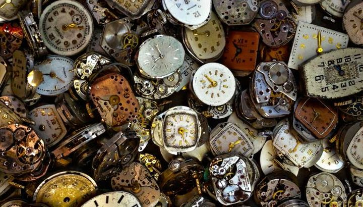 a pile of clocks showing the time