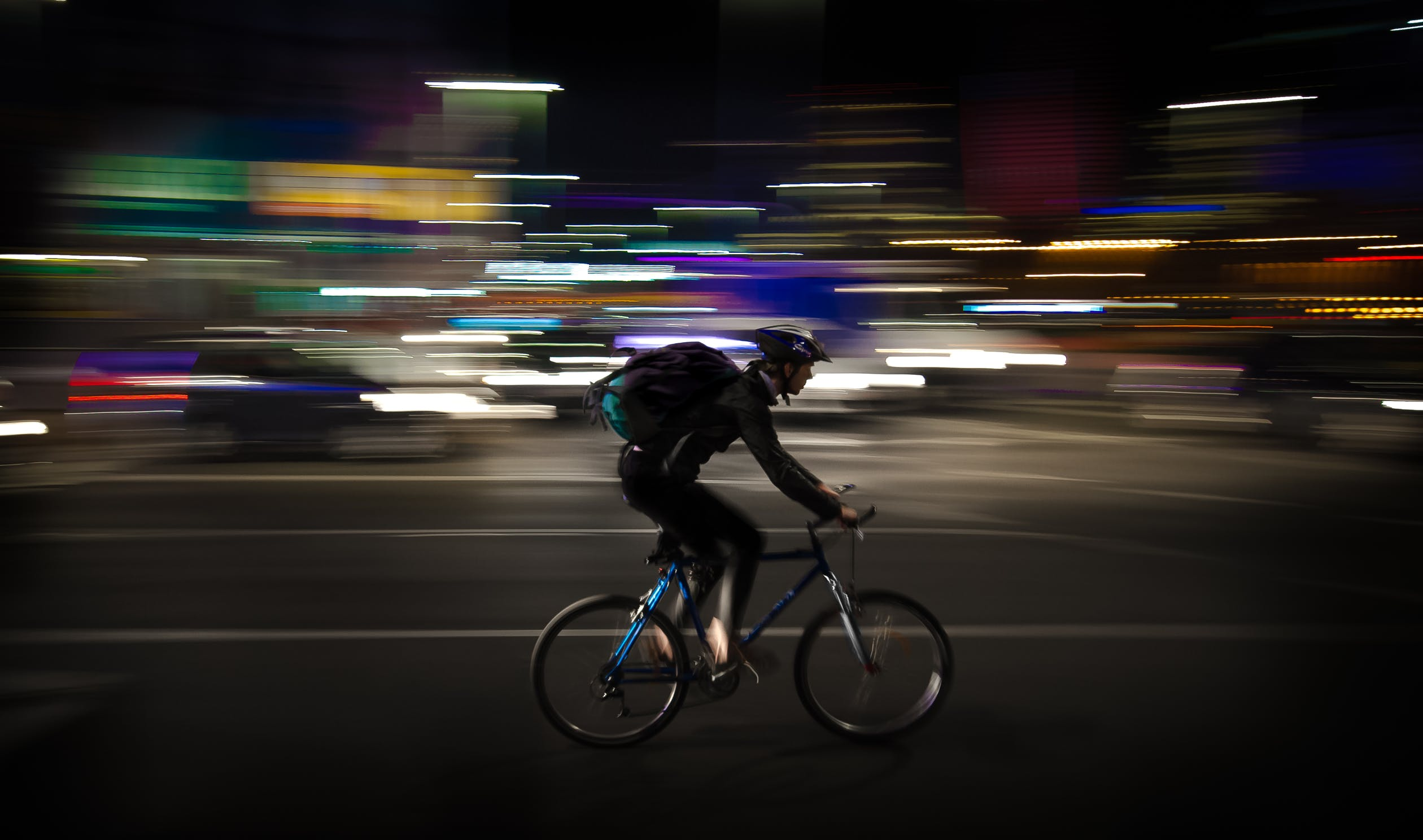 cyclist on road with helmet and bag on