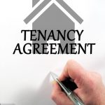 tenancy agreement document with someone holding a pen