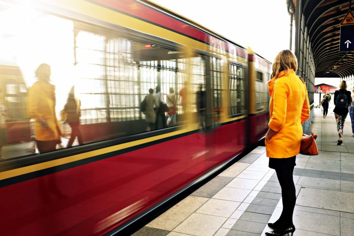 Tram and a woman standing on the platform in a yellow jacket