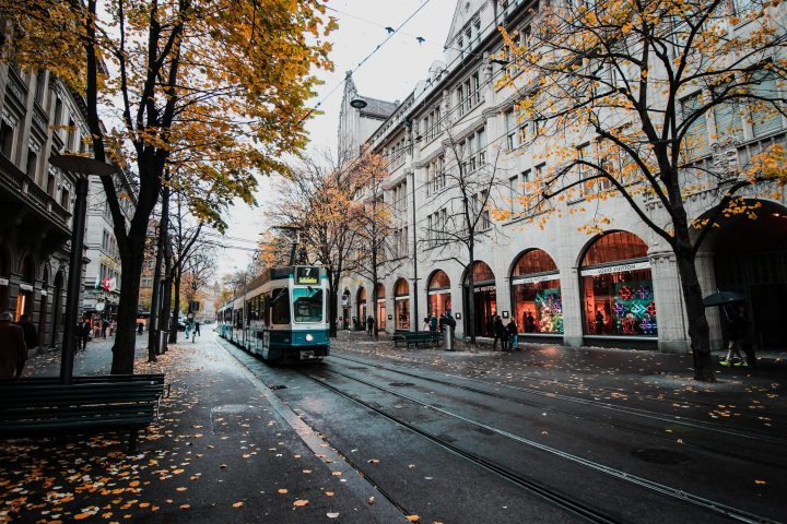 Tram travelling down a road with trees and shops
